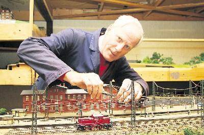 """Rainer Owsian prüft die neue Oberleitung. Erstmalig wird der Modelleisenbahnclub Poisental auch Elektrolokomotiven auf seiner 45 Quadratmeter großen Mittelgebirgsanlage rollen lassen. Sie ist für die Spurweite HO ausgelegt und im Stil der 1970er-Jahre gestaltet. Zum Kleinbahnfest soll sie als Attraktion mit der Anlage des Mohorner Modelleisenbahnclubs """"Triebischtalexpress"""" verbunden werden.Foto: Dorit Oehme"""
