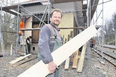 Rainer Malcherek trägt ein Brett zum Erneuern der Verschalung zum Gebäude des früheren Güterbodens am Bahnhof Seifersdorf. Foto: Egbert Kamprath